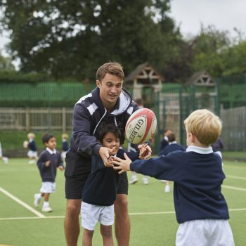 A rugby teacher teaching two kids how to pass a rugby ball.