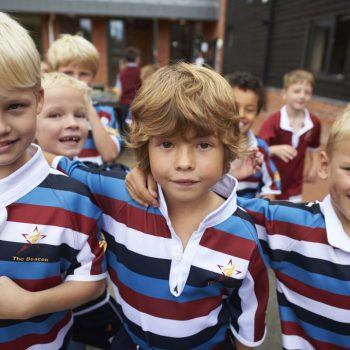 Three school boys wearing their rubgy uniforms and posing for a photo.