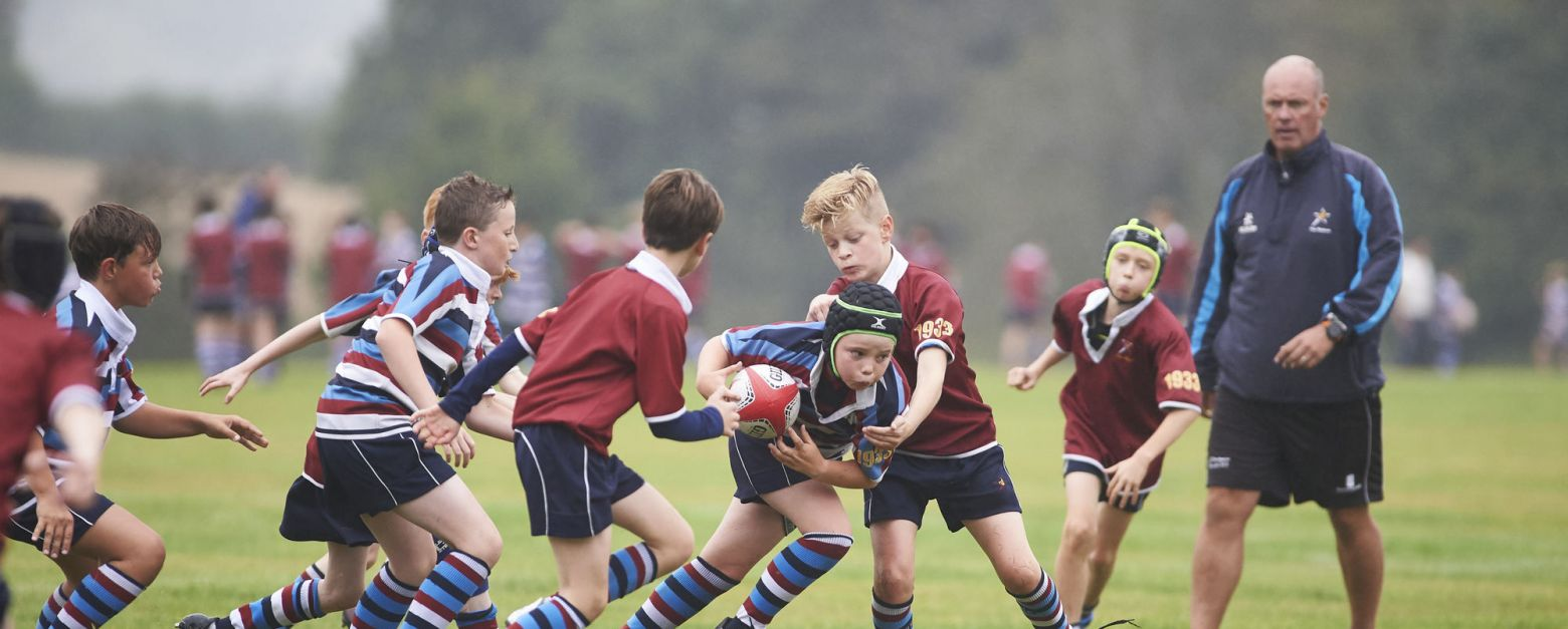 School boys play a game of rugby out on a field, one uniform in blue stripes, the other red jumpers.