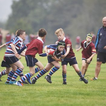 Two boy school rugby teams playing a game in a field.