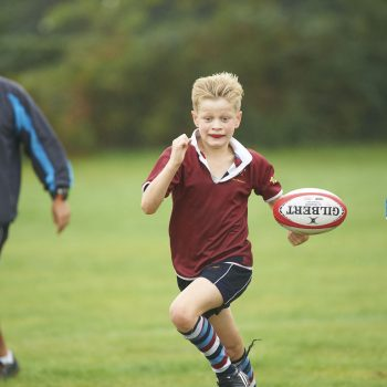 A blonde school boy running in a field after a rugby ball.