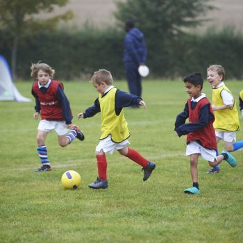 School boys, some in yellow bibs, some in red, playing football in a field.