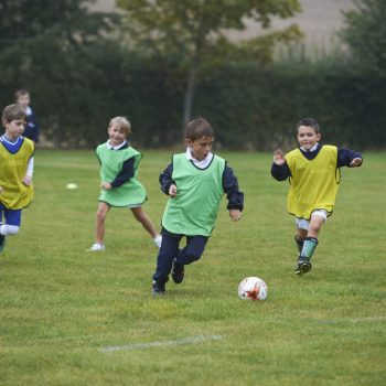 Two school football teams playing against each other, one in green bibs, the other in yellow bibs.