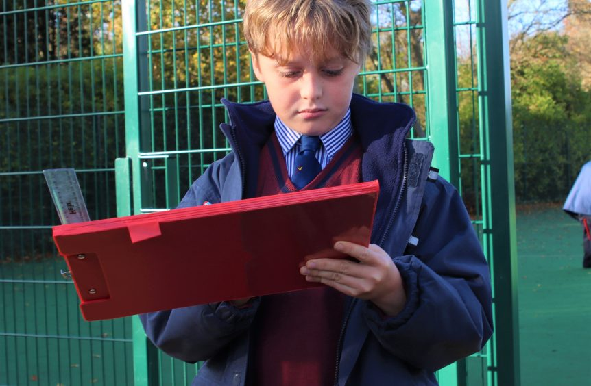 school boy outside looking at his clipboard