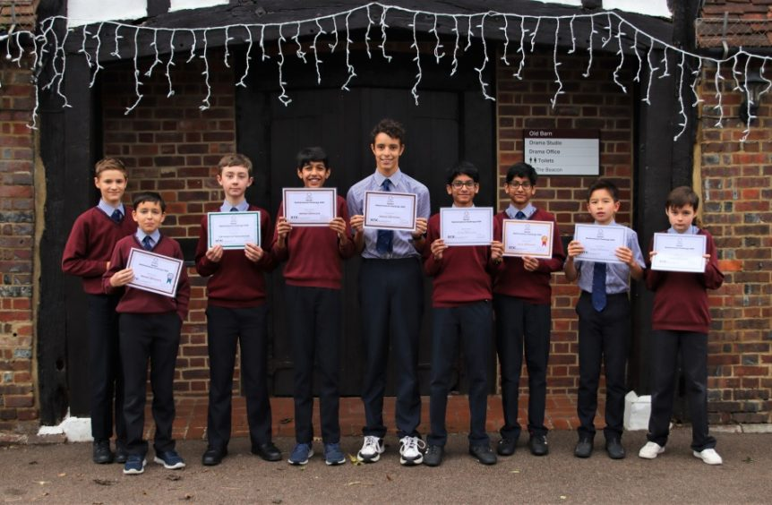 group of school boys holding up certificates