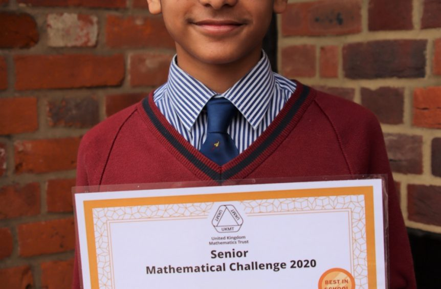 school boy wearing glasses and holding a gold certificate for a maths challenge