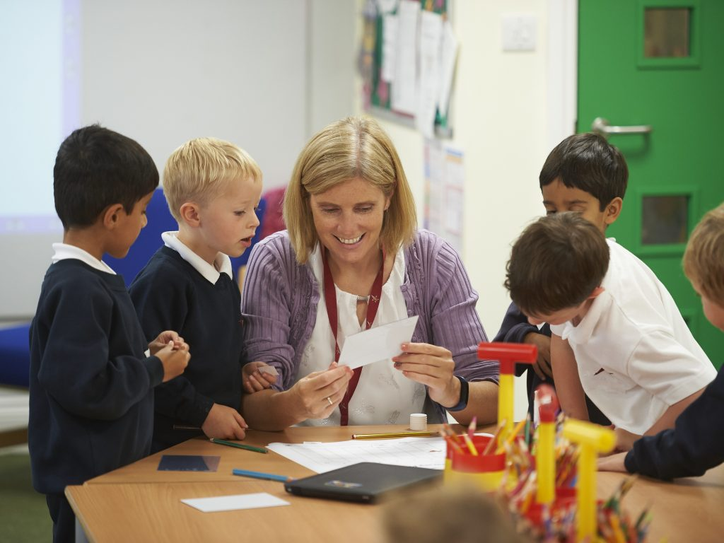 Five children in a classrooom, looking at something that their blonde teacher is sharing with them.