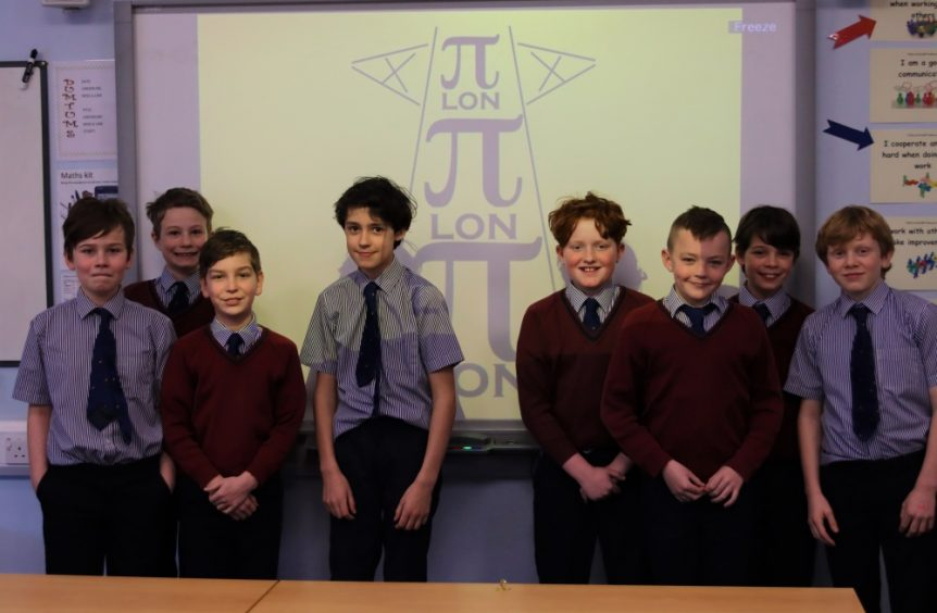group of eight school boys standing in front of interactive white board
