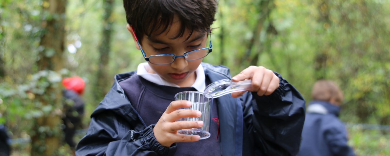 A boy wearing glasses, wearing a raincoat over their school uniform, looking at something in a plastic beaker with a magnifying glass.