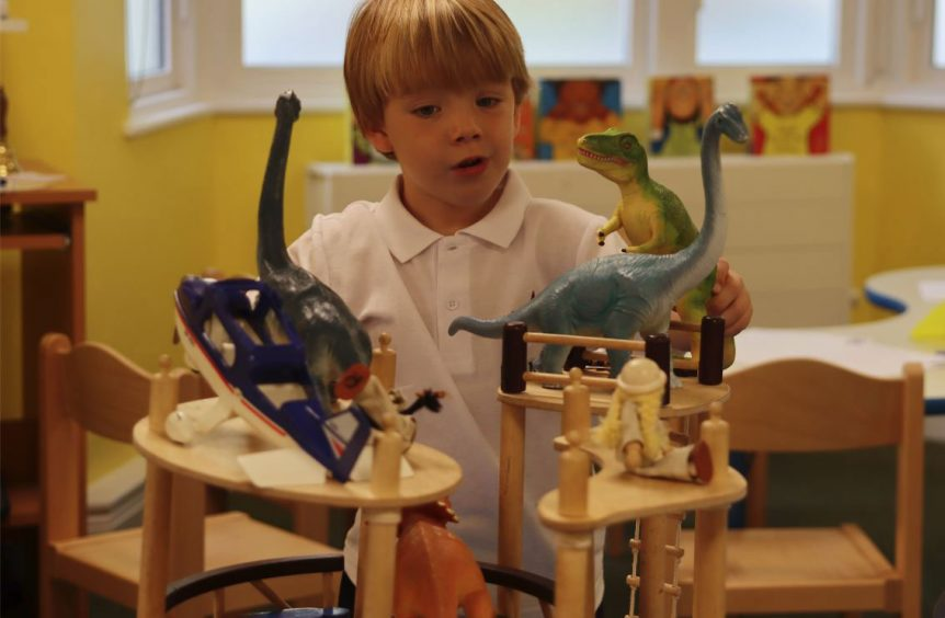 A boy playing with lots of dinosaur toys