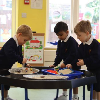 Boys talking around a table whilst they play