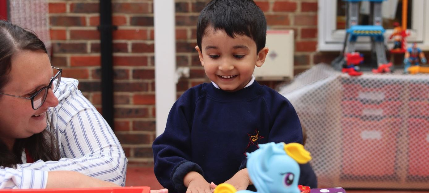 A young boy play with toys as a teacher looks on smiling