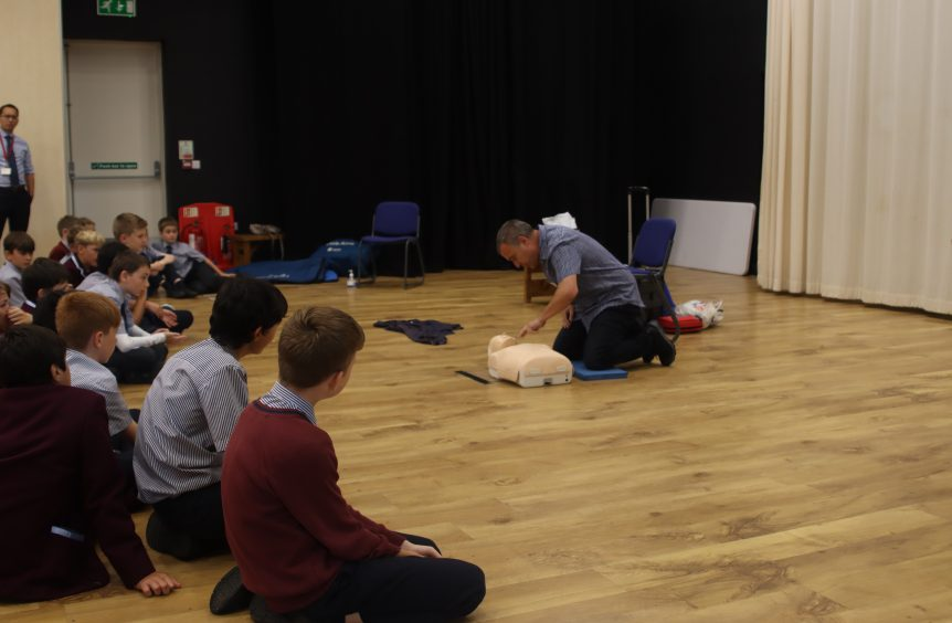 A first aid teacher demonstrates how to give chest compressions to the CPR doll