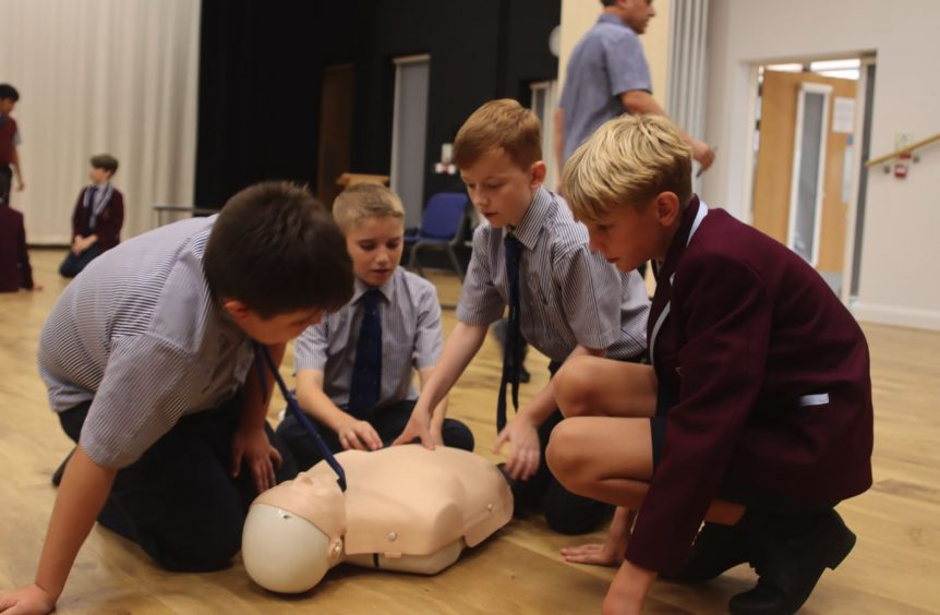 4 boys surround a CPR doll