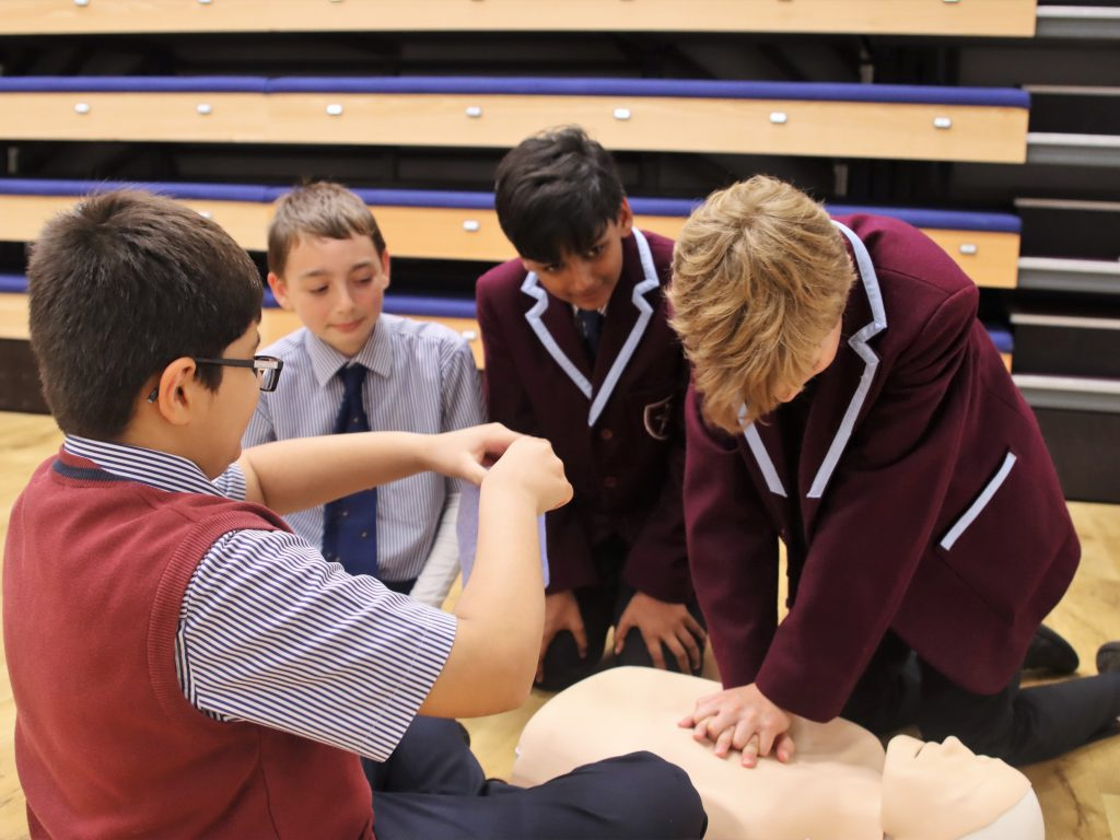 4 school boys practicing how to perform CPR