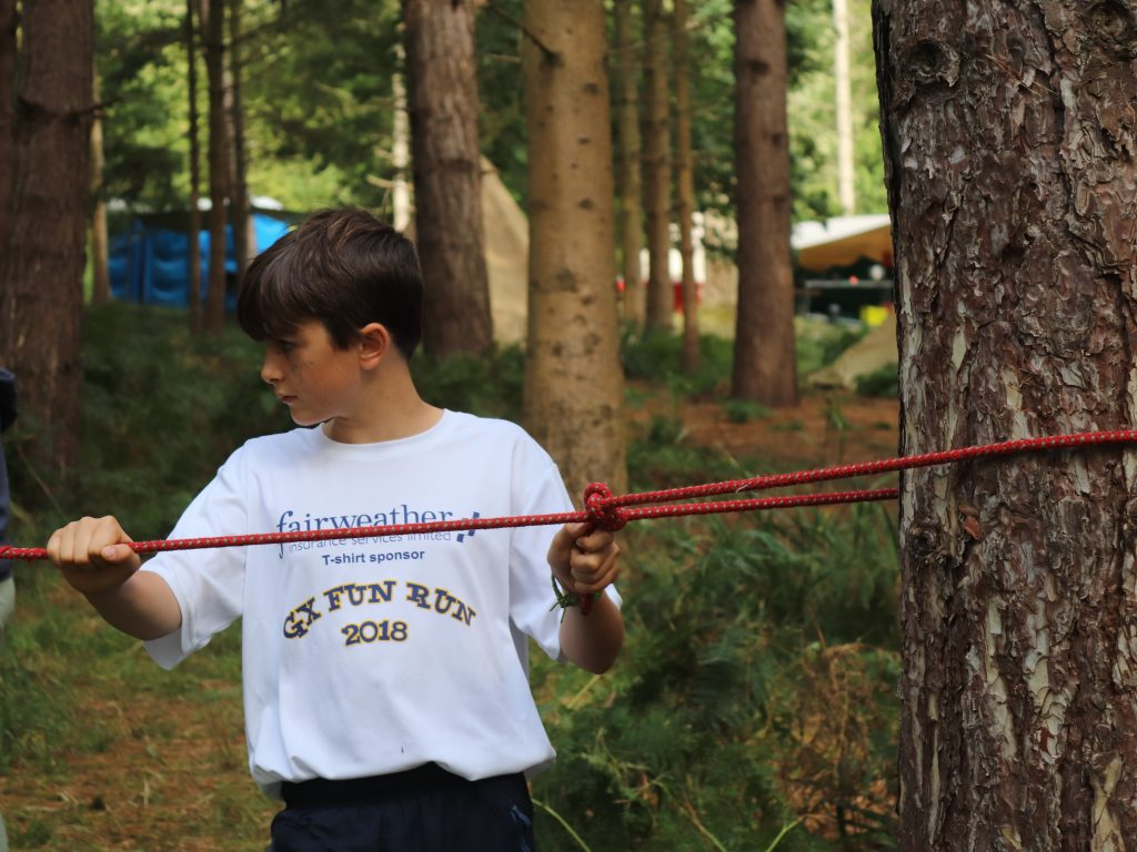 A boy pulling a rope across a tree trunk