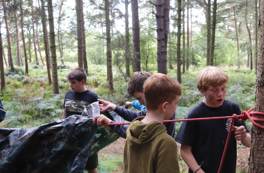 Boys setting up a tent in the woods