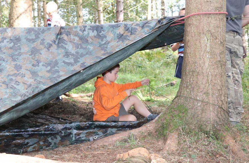 A young boy assembling a tent
