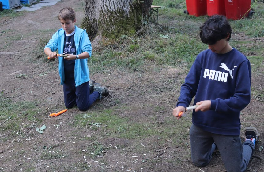 Boys practicing how to carve from wood