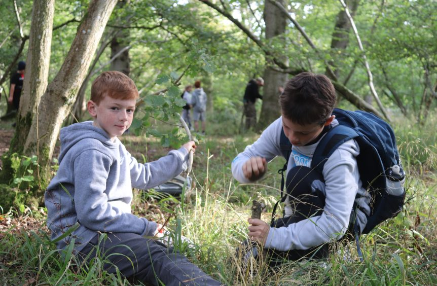 2 boys working on making a camp