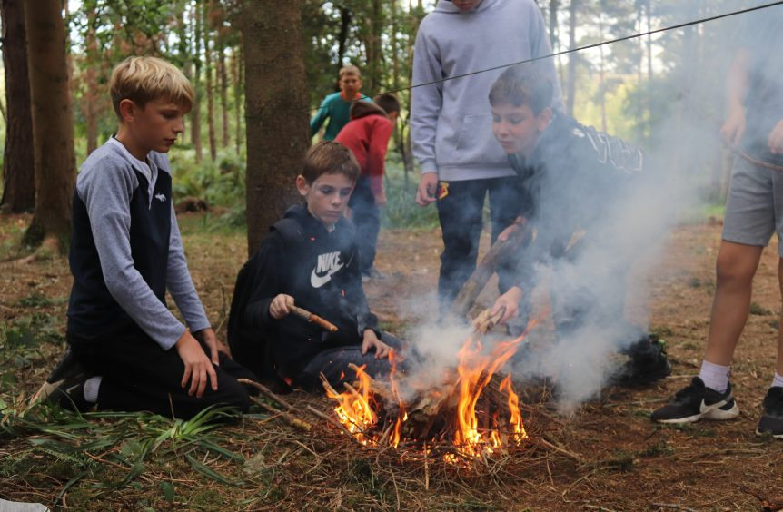4 boys working on making a fire using kindling in the woods