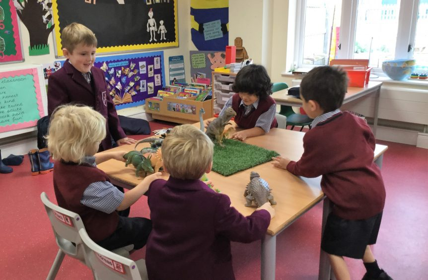 A group of boys playing with dinosaurs in the classroom
