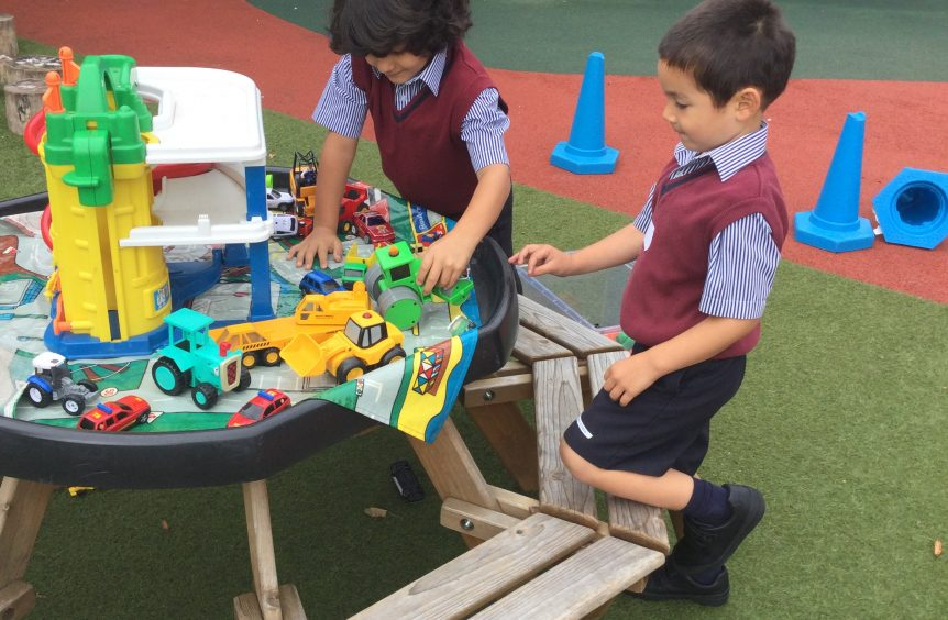 Boys playing with toys outside on a garden bench