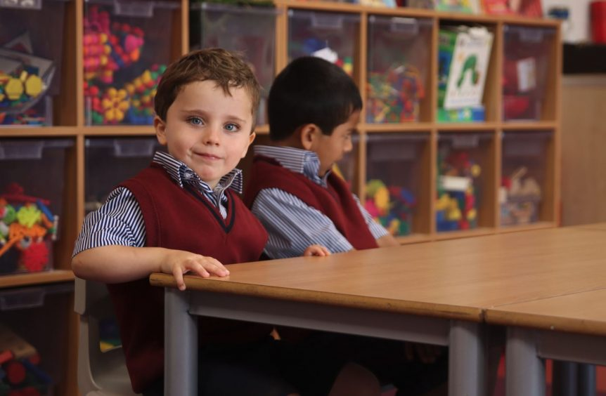 A young boy sitting down in class